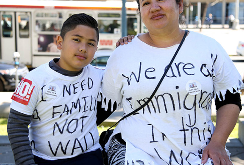 Tina Figueroa, 47, and her son Francisco from El Salvador post of a portrait at Justin Herman Plaza while they listen to speakers before marching down Market Street to call attention to immigrant rights and sanctuary cities on Monday May 1, 2017. Photo: Emma Marie Chiang
