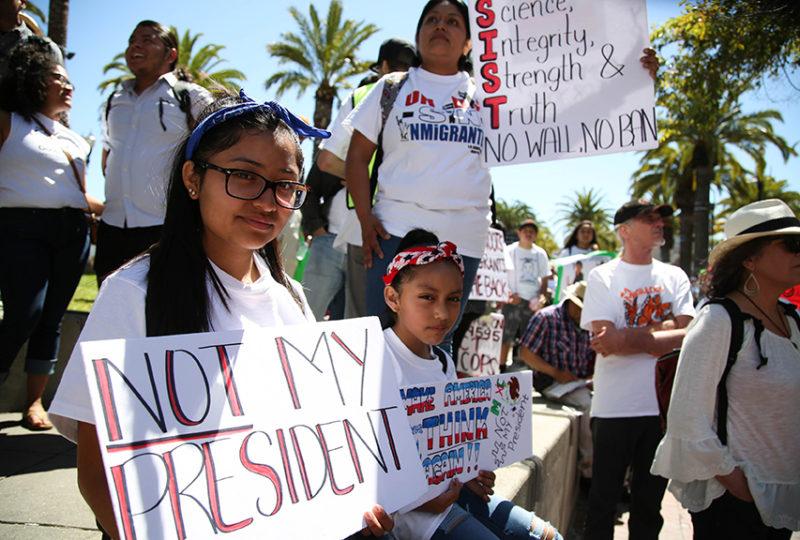 Quetzalli Muñoz (a la izquierda) de 16 años, y la hermana Minelly Guevara, de 9 años, sostienen un cartel mientras escuchan a los oradores que participaron en la marcha por el 'Día Sin Inmigrantes'.  Foto: Emma Chiang