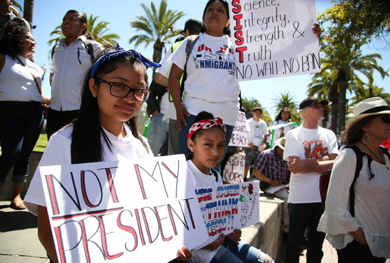 Quetzalli Munoz (left), 16, and sister Minelly Guevara, 9, hold signs while listening to speakers at Justin Herman Plaza before marching down Market Street to call attention to immigrant rights and sanctuary cities on May 1, 2017. Photo: Emma Marie Chiang