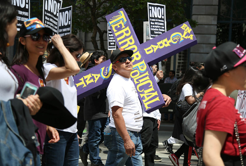 "Luis Poot, cousin of Luis Góngora Pat (the homeless man who was shot and killed by San Francisco Police on April 7, 2016) holds a purple cross while marching with thousands of demonstrators on Market Street for the ""A Day Without Immigrants"" May Day march on May 1, 2017. Photo: Emma Marie Chiang"