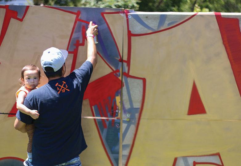 Precita Eyes llevó a cabo su Urban Youth Arts Festival el 22 de julio de 2017 en el parque Precita. Un artista perteneciente al grupo que se hace llamar AJ Mob pinta un mural con aerosol para honrar a su amigo Chris Masis, alias Cams, que se suicidó el mes pasado. Foto: Erica Marquez