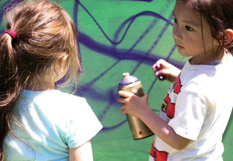 Lina (izquierda) y Corbin de 4 y 3 años de edad, respectivamente, pintan detrás de un lienzo improvisado. Foto: Erica Marquez.