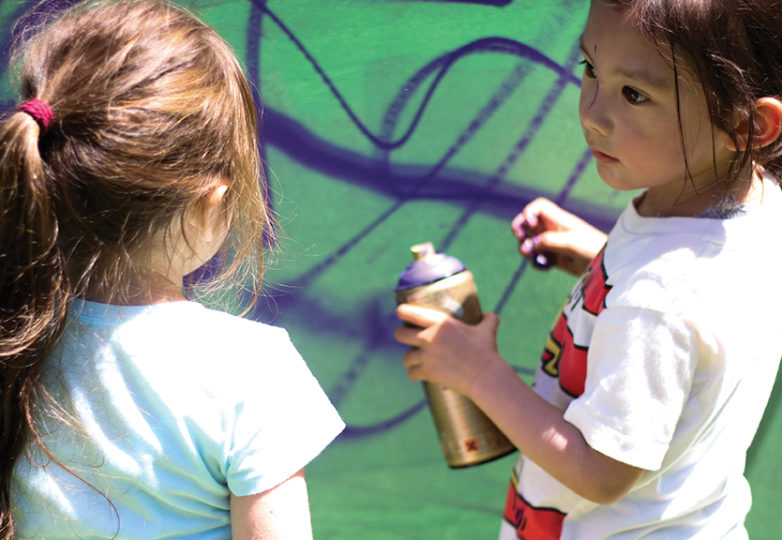 Four-year-old Lina (left) and Corbin, 3, paint behind a makeshift canvas at Precita park. Photo: Erica Marquez.