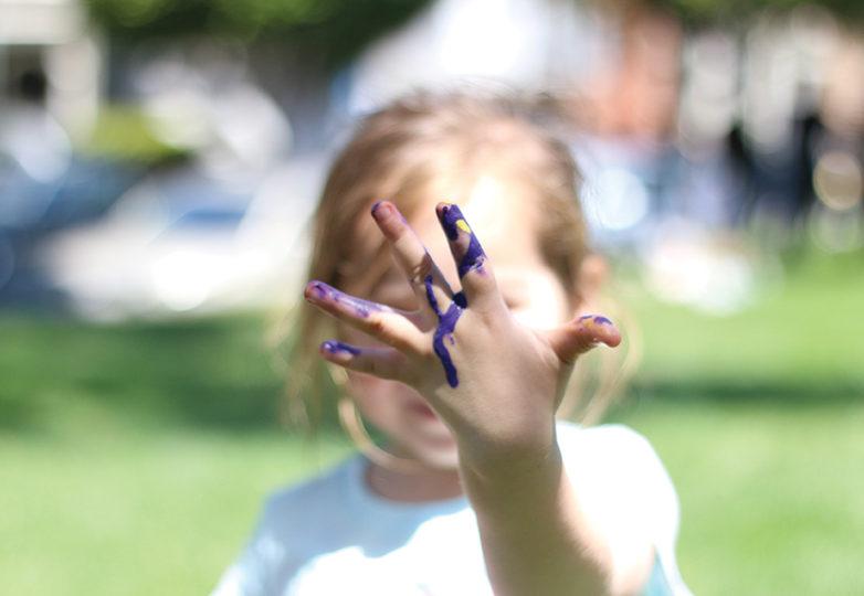 Durante el  Urban Youth Arts Festival de Precita Eyes, Lina, de 4 años de edad, enseña sus manos pintadas. Foto: Erica Marquez.