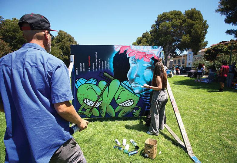 Fofia Fisher, de 14 años de edad, pinta con su papá Pancho Fischer, de 43 y chileno, durante el Urban Youth Arts Festival que Precita Eyes llevó a cabo el 22 de julio de 2017 en el parque Precita. Foto: Erica Marquez