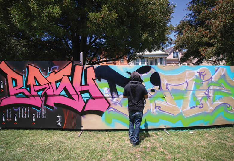 An anonymous artist spray paints on a makeshift canvas. Photo: Erica Marquez.