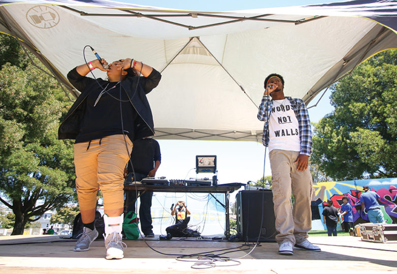 "Harmony Moses, 18, and Chance Robinson, 19, rap on stage at the Precita Park rapping ""hands up don't shoot. Moses and Robinson are a part of Hip-hop through History, a program sponsored by Spotify. Photo: Erica Marquez."