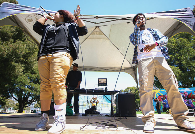 "Harmony Moses, 18, and Chance Robinson, 19, rap on stage at the Precita Park rapping ""hands up don't shoot. Moses and Robinson are a part of Hip-hop through History, a program sponsored by Spotify. Photo by Erica Marquez."