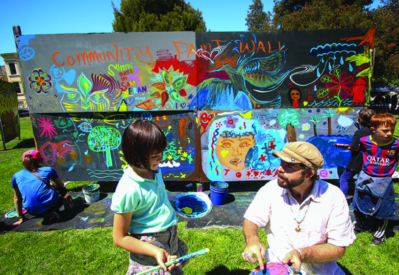 Mateja, de 7 años de edad, y Robert Louthan, de 31, juntan pintura en la sección de niños durante el festival de arte. Foto: Erica Marquez