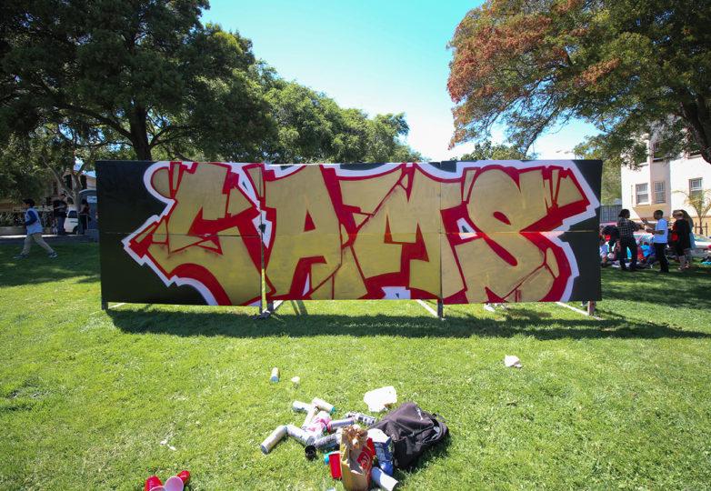 El grupo AJ Mob pinta un mural con aerosol para honrar a su amigo Chris Masis, alias Cams, que se suicidó el mes pasado, esto durante el festival organizado por Precita Eyes. Foto por Erica Marquez.