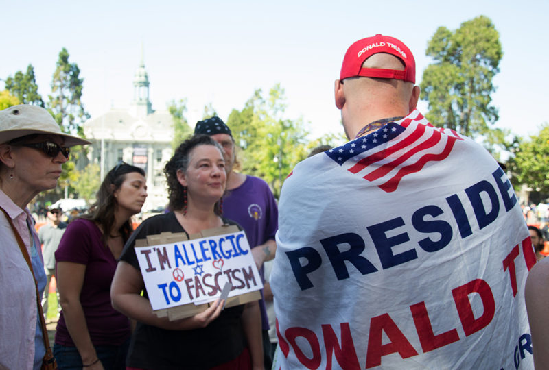 A counter demonstrator listens to a Trump supporter, draped in a flag, at MLK Civic Center park in Berkeley, Sunday Aug. 27. Photo: Mabel Jimenez