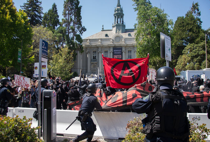 A Berkeley police officers attempts to pull a banner from the Antifa crowd during a demonstration at MLK Civic Center. The officer was unable to pull the banner and retreated soon after. Photo: Mabel Jimenez