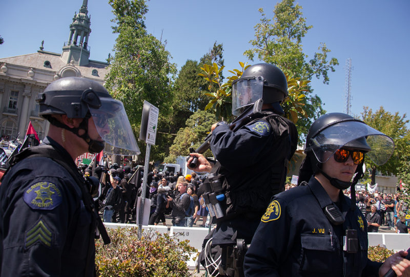 A Berkeley Police officer prepares to fire teargas against the crowd of antifa outside of MLK Civic Center Park in Berkeley. Photo: Mabel Jimenez