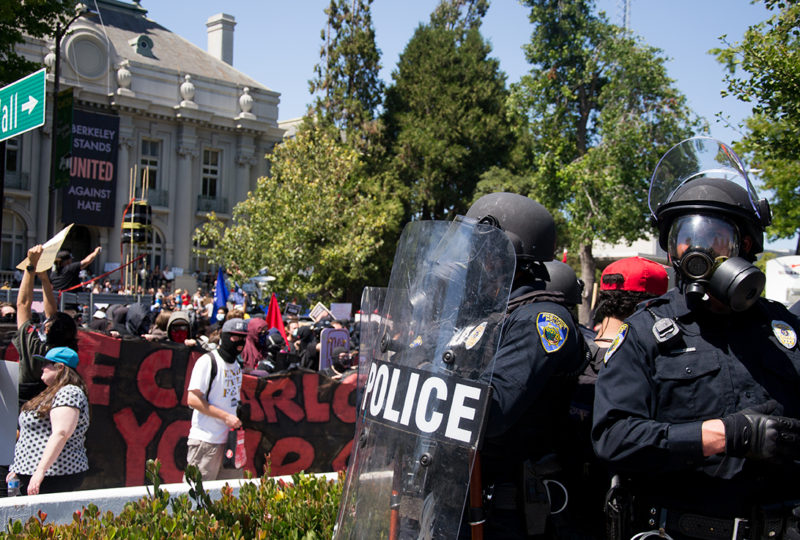 Police officers in riot gear attempt to contain the crowd that marched from UC Berkeley's Crescent Lawn to MLK Civic Center to counter protest an Anti-Marxist rally, which was cancelled days prior. Photo: Mabel Jimenez