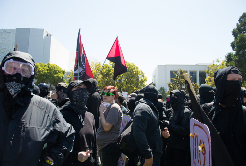 A crowd of antifa Black Bloc counter protesters crossed a boundary around MLK Civic Center park in Berkeley, bypassing checkpoints meant to keep forbidden items outside of the rally area. Photo: Mabel Jimenez