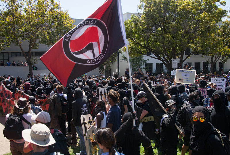 A crowd of antifa black block counter protesters crossed a boundary around MLK Civic Center park in Berkeley, bypassing checkpoints meant to keep forbidden items outside of the rally area. Photo: Mabel Jimenez