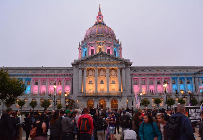 En respuesta a la amenaza de Trump de vetar a las personas transgénero de participar en la milicia, el ayuntamiento fue iluminado con los colores de la bandera transgénero (rosa, azul y blanco). Foto: Jay Garcia