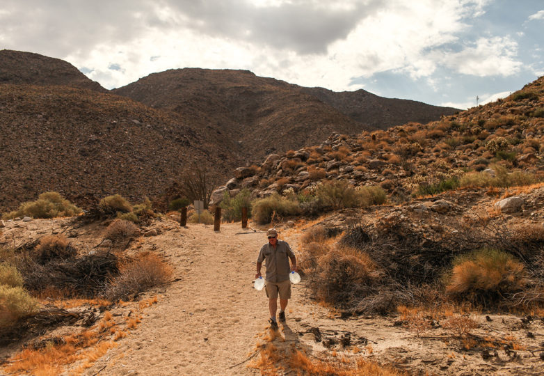 Rob Fryer, a volunteer with the nonprofit organization Water Stations, carries gallons of water toward a water station for migrants crossing the U.S.-Mexico border through the Carrizo Gorge in the Imperial Valley outside of Ocotillo, California on July 15, 2017. Photo: Joel Angel Juárez