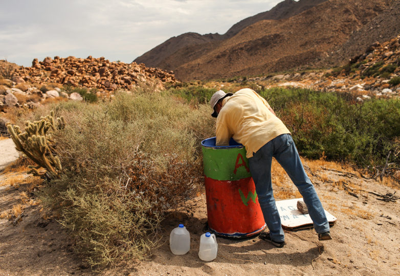 Don Whitney, a volunteer with Water Stations, fills a container with gallons of water for migrants crossing the US-Mexico border through the Carrizo Gorge in the Imperial Valley outside of Ocotillo, California on July 15, 2017. Photo: Joel Angel Juarez