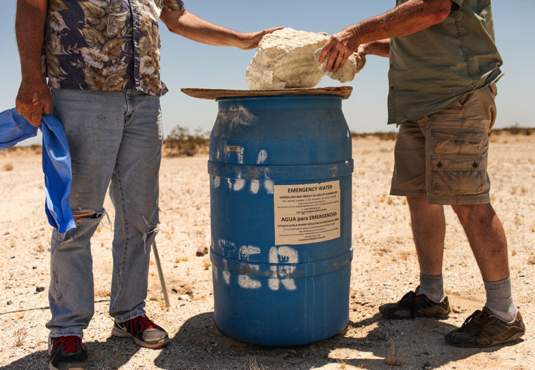 John Hunter (left) and Rob Fryer (right) place stones adding weight to close a water station within a military bombing range located in the Imperial Valley desert outside Plaster City, California on July 1, 2017. Photo: Joel Angel Juarez