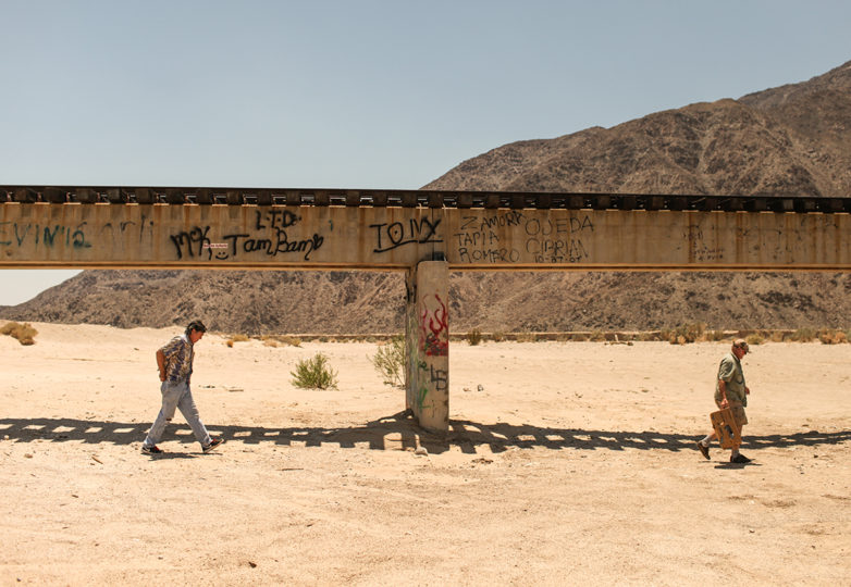 John Hunter (left) and Rob Fryer (right) walk past a railroad bridge within a military bombing range located in the Imperial Valley desert outside Plaster City, California on July 1, 2017. The site is located 15 miles north of the US-Mexico border. Photo: Joel Angel Juarez