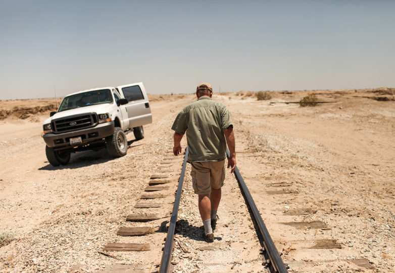 Rob Fryer, a volunteer with Water Stations, walks along a railroad after completing a station refill within a military bombing range located in the Imperial Valley desert outside Plaster City, California on July 1, 2017. Photo: Joel Angel Juarez