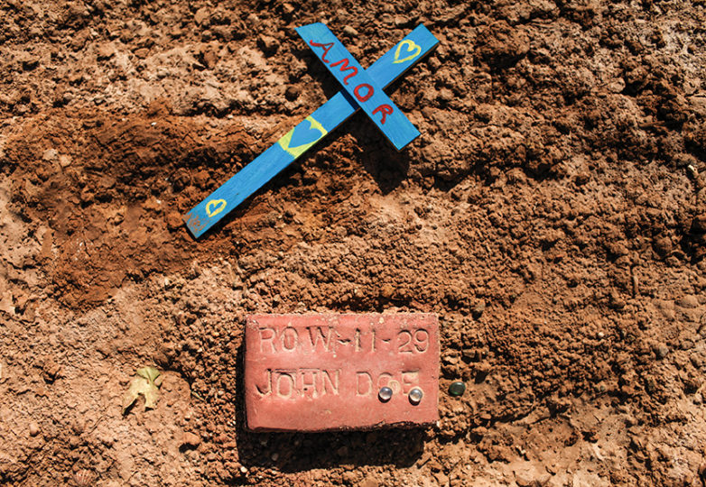 A cross and a brick lie on soil indicating a burial site of an unidentified migrant in an unmarked dirt lot behind the Terrace Park Cemetery in Holtville, California on July 1, 2017. The lot contains the remains of hundreds of unidentified migrants who died crossing the U.S.-México border in the Imperial Valley desert. Temperatures in the area reach above 110 degrees Fahrenheit in the summer months posing high risks of heat casualties and death. Photo: Joel Angel Juárez