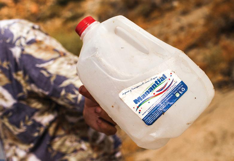John William Hunter, fundador de la organización Water Stations, sostiene un galón vacío de agua que un inmigrante dejó en su cruce por la frontera México-EEUU, por Carrizo Gorge y el Parque Estatal Desierto Anza Borrego. Foto: Joel Angel Juárez