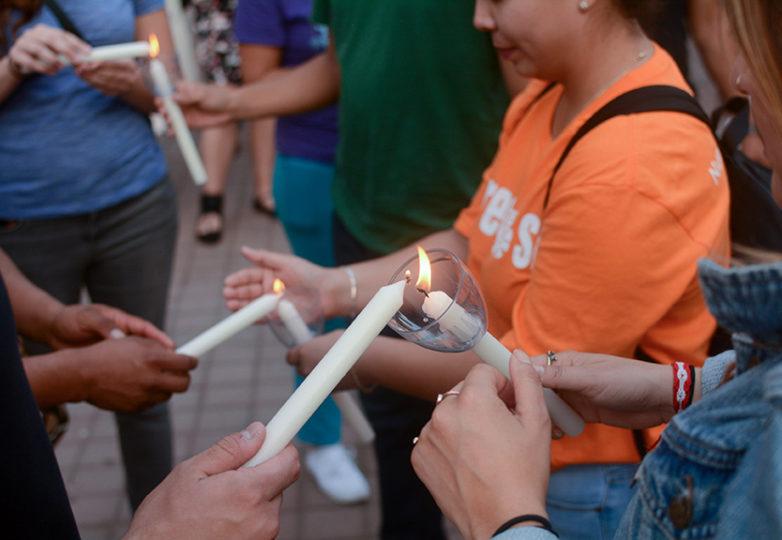 Receptores de DACA encienden velas en la vigilia de emergencia organizada en Oakland. Foto: Aaron Levy-Wolins