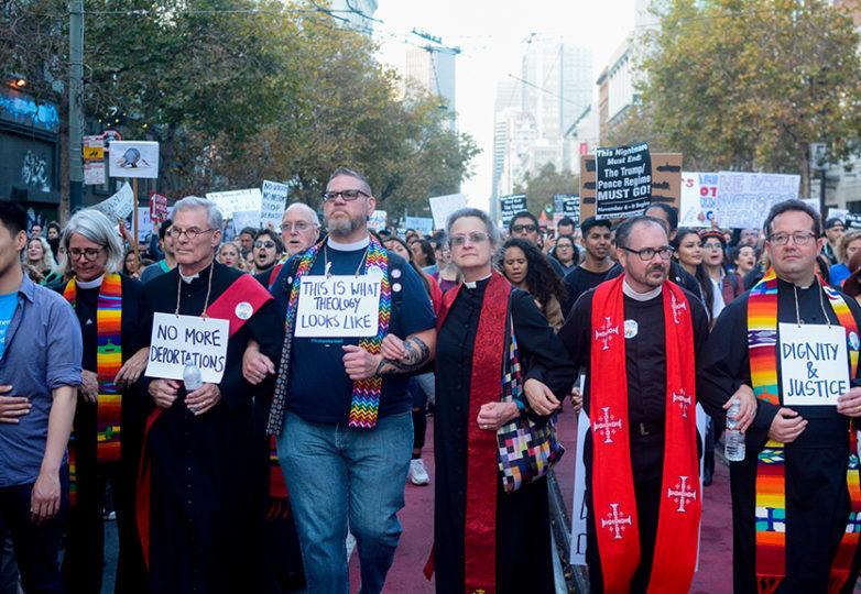 Líderes religiosos marchan por la calle Market con los brazos entrelazados entre sí, en una marcha de emergencia organizada tras la decisión de Trump de rescindir el programa. Foto: Aaron Levy-Wolins