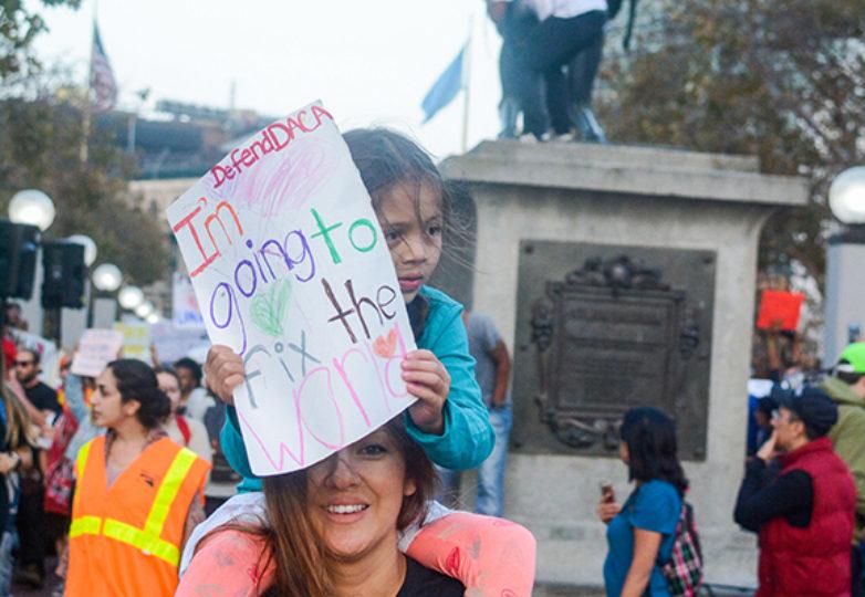 Denise Sánchez, de 34 años, una estudiante de salud humana, en el Contra Costa College y madre soltera, lleva consigo a su hija Mikayla, de 6 años de edad, quien cubre su rostro con un cartel, en la marcha de apoyo a los receptores de DACA. Foto: Aaron Levy-Wolins