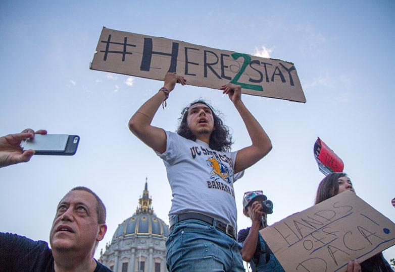 El estudiante de la UC Santa Cruz, Michael Carbonaro, sostiene un cartel en el que se lee #AquiParaQuedarnos frente al ayuntamiento de San Francisco, el 5 de septiembre de 2017. Foto: Drago Rentería