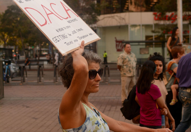 Louise Chegwidden, 57, a physical therapist from Oakland, Calif., and an immigrant from Australia who just obtained citizenship after living in the US for 30 years, holds a sign at an emergency vigil for DACA recipients at Frank Ogawa Plaza in Oakland, Calif. on Thursday, August 31, 2017.  The vigil was called amid reports that in the coming days, even as soon as tomorrow, President Donald Trump will end the DACA program. Photo: Aaron Levy-Wolins
