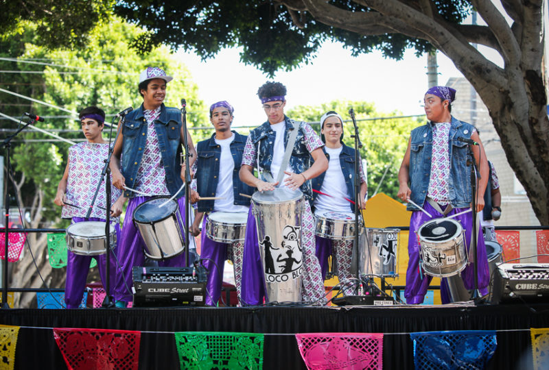 Loco Bloco group performs dance and music on Brava Stage at 24th and Hampshire Streets during the Calle 24 Fiesta de las Américas festival in San Francisco's Mission District, Sunday, Sept. 17, 2017. (Photo by Ekevara Kitpowsong)