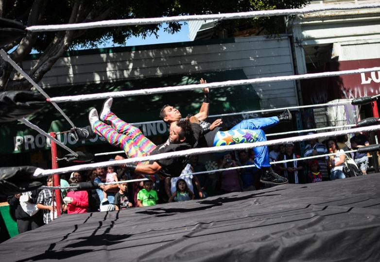 Los luchadores de Lucha Libre, Willy y Loco del Campanario pelean en el ring del escenario ubicado en la calle 24.