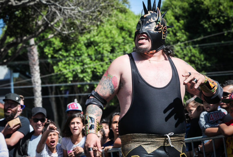 People cheer as a Lucha Libre wrestler Mr. Punk walks on the rin