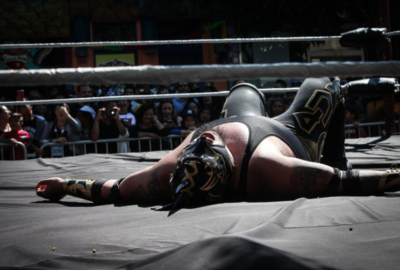 A Lucha Libre wrestler Mr. Punk lays on his back in the ring dur