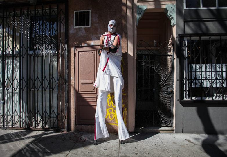 El artista en zancos portando una mascara de luchador, Ernesto Sopprani parado en la calle 24 durante la Fiesta de las Américas el sábado 17 de septiembre en la Misión.