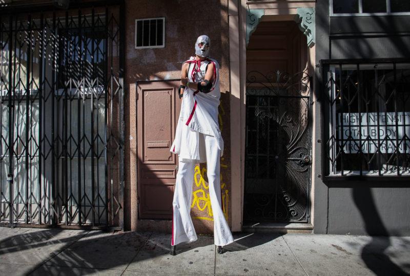 A stilt performer wearing a Lucha Libre mask Ernesto Sopprani st