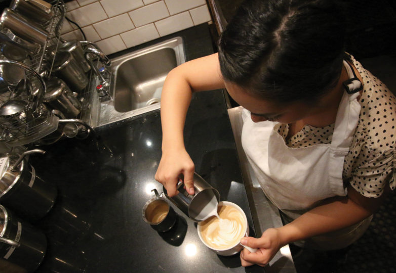A barista at Temo's Café prepares a coffee drink for a customer. Photo: Erica Marquez
