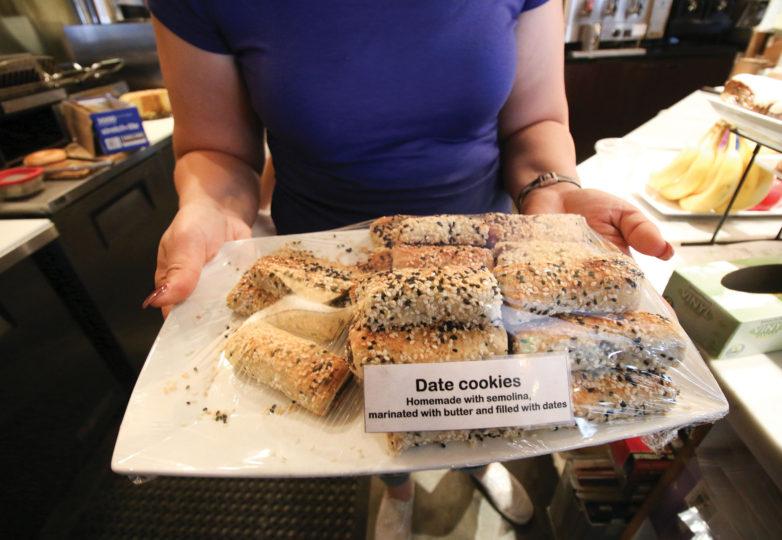 Lamea Abuelrous, dueña de Temo's Café, sostiene unas galletas de dátiles hechas en casa que ofrece a la venta en su negocio. Foto: Erica Marquez
