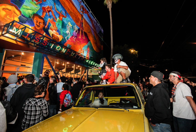 "People  watch the ""Fogo Na Roupa"" music performance in front of the Mission Cultural Center for Latino Arts during the Mission Día de Muertos Celebration, Nov. 2, 2017. Photo: Ekevara Kitpowsong"