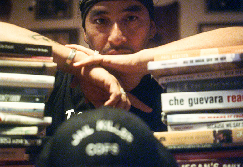 Equipto standing with books he has read on  Oct. 10 in the living room of the house he grew up in Mission District. Photo: Daniel Valencia