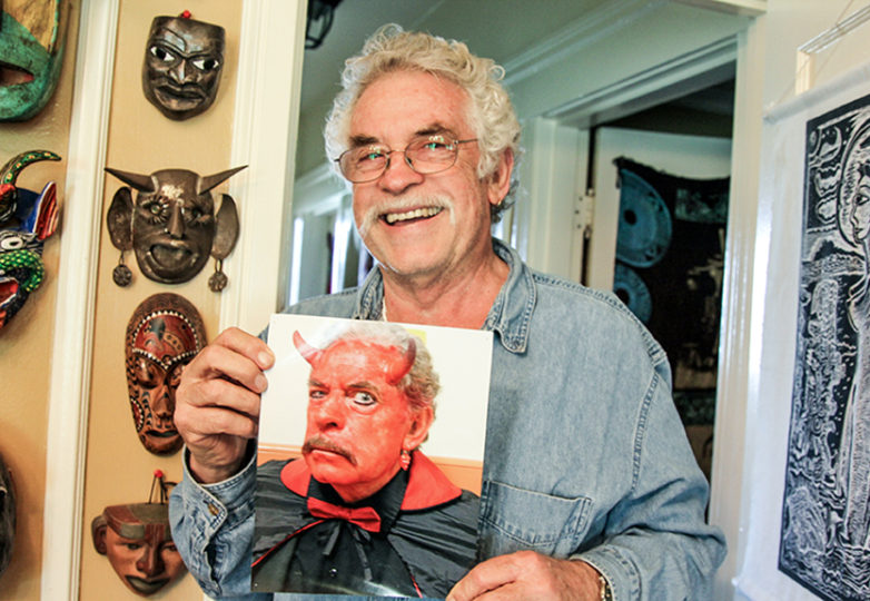 Carlos Baron poses with an older portrait of himself portraying the devil in past years with La Posarela in his home in Daly City on Nov. 14. Photo: Adelyna Tirado