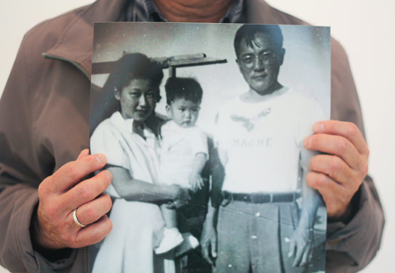 Art Sato holds a photo from his childhood of himself, his mother Kimiye and father Tomomi while they were imprisoned at the Amache incarceration camp. Photo: Alexis Terrazas