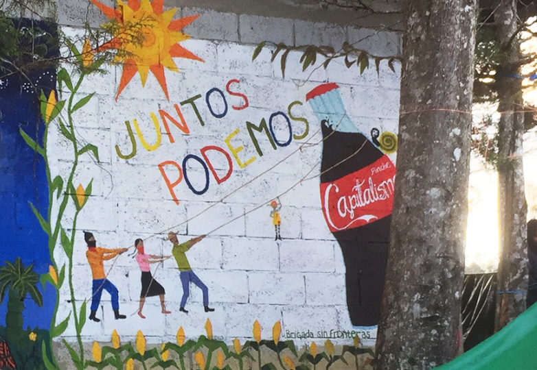 En un mural en la capital zapatista, Oventik en Chiapas, un zapatista, una mujer, un hombre y un niño acaban con el capitalismo en forma de una Coca Cola. Foto: John Carson