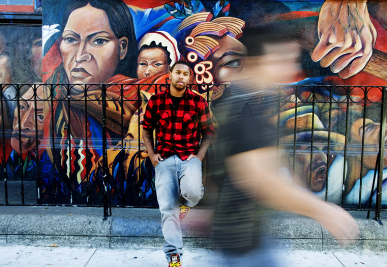 "Filmmaker Jay Francisco López, creator of ""Love Cecy,"" poses for a portrait in front of the mural ""500 Years of Resistance"" painted by Isaias Mata. Photo: Mabel Jiménez"
