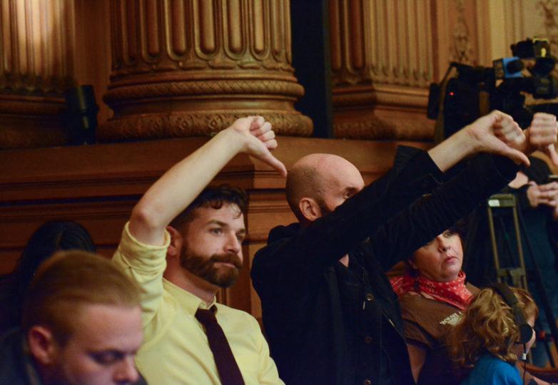 Opositores de London Breed, ex alcadesa interina de San Francisco, con pulgares hacia abajo, en señal de desaprobación, durante la sesión pública de la Junta de Supervisores. Foto: Aaron Levy-Wolins