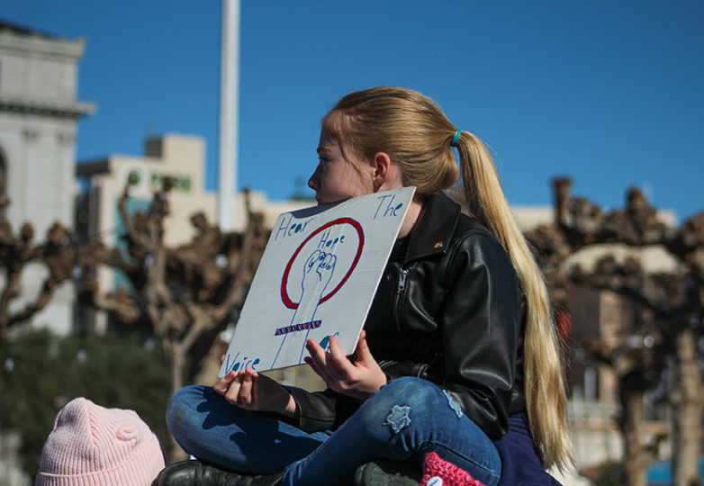 "A young girl sits on top of a structure at the Civic Center playground holding a poster reading ""Hear The Hope"" at the second annual Bay Area Women's March in Civic Center Plaza on Jan. 20, 2018.  Photo: Jocelyn Carranza"