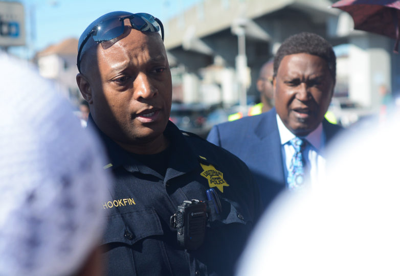 Oakland Police Lt. Bobby Hookfin speaks with the family of Sahleem Tindle, promising to do anything he can to help the family during a vigil-protest in front of the West Oakland BART Station on Feb. 13, 2018. The vigil-protest was in honor of Tindle, who was killed by BART Police on Jan. 3, and to charge the officer, Joseph Mateu, who shot Tindle, with murder. Photo Aaron Levy-Wolins